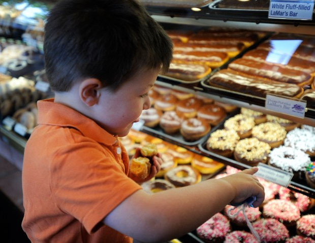 LaMar's Donuts at 6th and Kalamath St. were handing out free donuts early Friday morning to customer because today is National Donut Day. Photo of little Zane Peterson, age 3, Denver. has his tongue hanging out a little looking at the other donust.June 3, 2011. John/Prieto The Denver Post. .