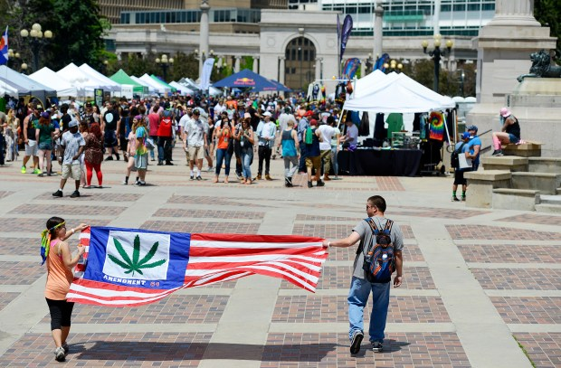 Allison Vanderveen and her brother, Ryan Vanderveen, walk with a flag during the Denver 420 Rally held Saturday at Civic Center Park.