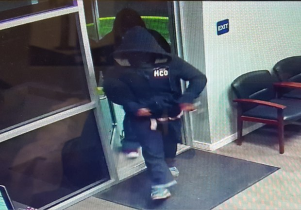 The first person of interest, shown in front of this photo, was wearing a dark-colored full-zip hooded sweatshirt, a red and white horizontal stripe shirt, blue jeans and gray shoes with white stripes and blue shoelaces.