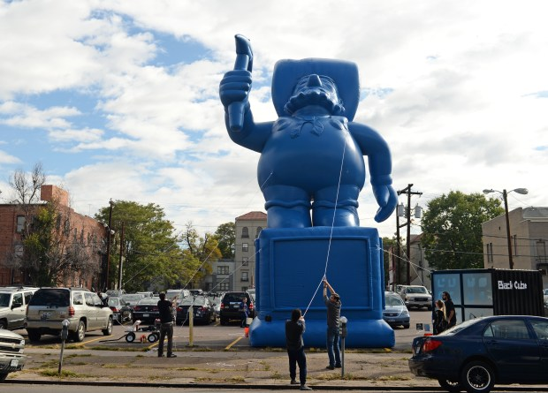 """A 40-foot tall Prospector """"sculpture"""" is being inflated in parking lot on Grant Street across from State Capitol, October 23, 2015. The sculpture, by artist Chad Person, is part of a pop-up exhibition curated by Black Cube. (RJ Sangosti/The Denver Post)"""