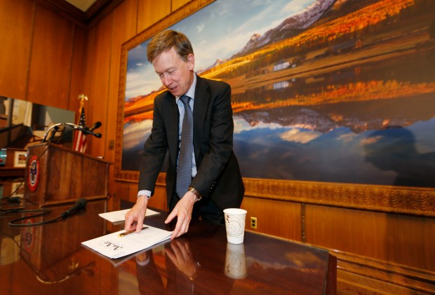 Gov. John Hickenlooper reaches down to pick a bill he signed to gradually allow grocery stores to sell full-strength beer, liquor and wine on Friday, in Denver. The law, which makes the biggest change to state liquor laws since the end of Prohibition, sets up a 20-year period for grocers to slowly acquire liquor licenses. Colorado's largest grocers say the change will take too long and vow to ask voters this fall for speedier changes.