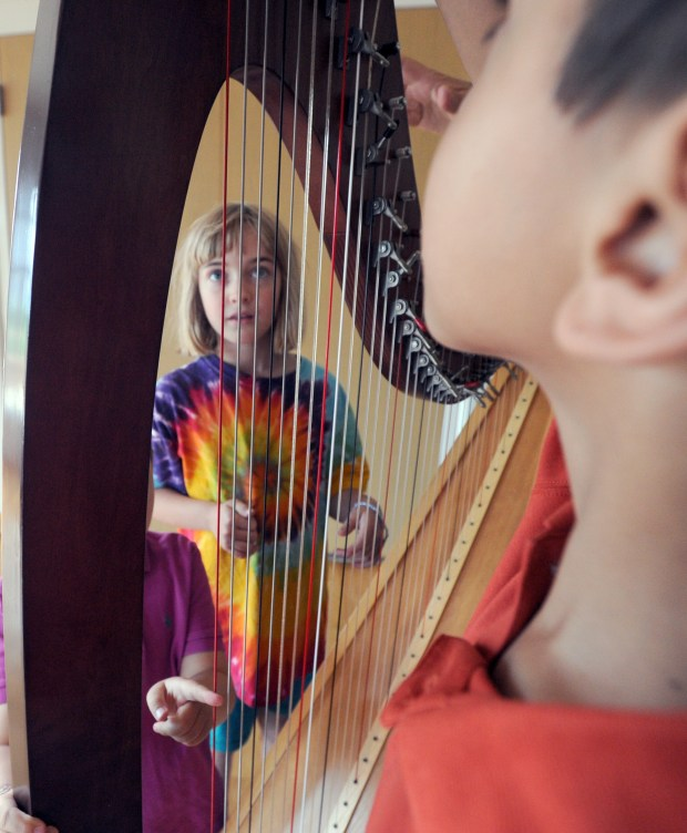 "Jazzy Marshall watches how the strings move on the harp played by Pam Eldridge at a ""Brainsong"" concert."