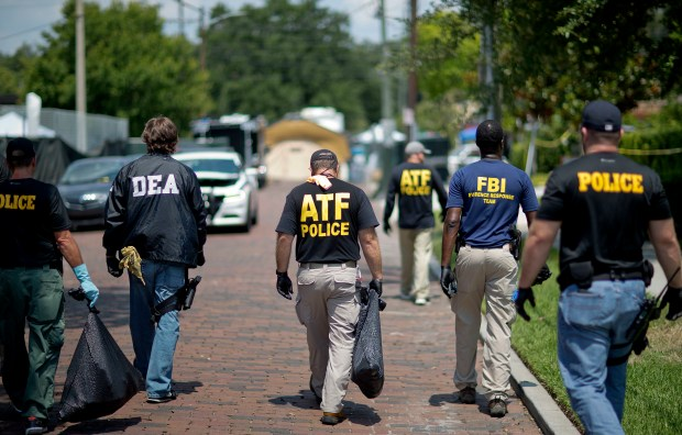Federal and local law enforcement officials walk through the street next to the scene of a mass shooting at a nightclub Monday, June 13, 2016, in Orlando, Fla.