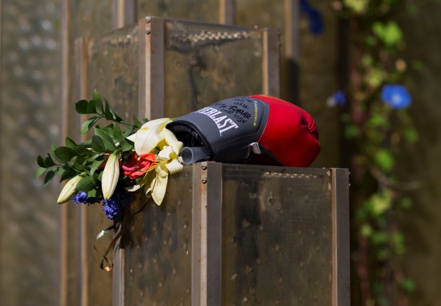 Flowers and a boxing glove are left at a makeshift memorial to Muhammad Ali at the Muhammad Ali Center, Monday, in Louisville, Ky. The president of Turkey and king of Jordan joined the long line of world leaders, religious figures and superstars set to speak at Ali's funeral Friday.