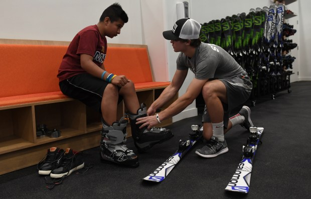 CENTENNIAL, CO - JUNE 20: Ski valet Cole Von Feldt, right, helps fit Joshua Herrera, 11, into a pair of ski boots. This will be the first time that Herrera has ever tried skiing. Instructors work with students at the new Snobahn Indoor Ski and Snowboard center in Centennial on Monday, June 20, 2016. The facility, located on the Streets at SouthGlenn shopping center, will host it's grand opening on Friday, June 24, 2016.(Photo by Kathryn Scott Osler/The Denver Post)