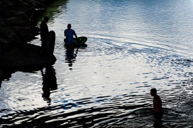 Three men enter the South Platte River with inflatable inner tubes with the intention of riding down the rapids at Confluence Park on Wednesday, Aug. 20, 2014 in Denver, Colorado.