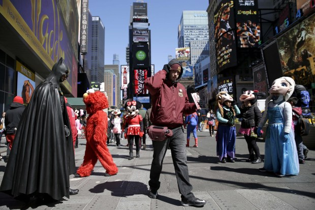 A bus-tour ticket seller, center, walks through a group of costumed characters in Times Square in New York.