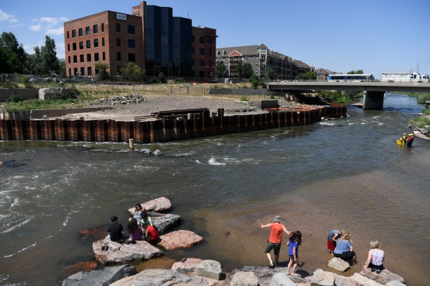 People last week cool off across fromthe unfinished improvement project at Confluence Park last week. The 15th Street bridge, right, crosses the South Platte River, near where Cherry Creek, lower right, feeds into it.