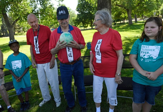 LITTLETON, CO - JULY 13: Senior Lois Moersen, second from right, passes a plastic ball to Ken Gould, middle, while YMCA summer campers Jazmin Baker, 10, right, and Devonne Mills, 12, far left, look on during an Aikido martial arts class at Littles Creek Park on July 13, 2016 in Littleton, Colorado. Children from Littleton YMCA summer camp and seniors from Highline Place, a memory care community, participated in the group martial arts class. The seniors, who suffer with dementia, and the summer camp kids practice together to learn from and help one another. Aikido helps with cognition and mood for people suffering with dementia and at the same time it helps to teach young kids self confidence. Banzai is Japanese for a patriotic cry or joyous shout. (Photo by Helen H. Richardson/The Denver Post)