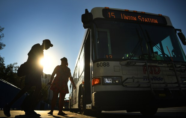 Commuters get on a bus along Colfax Avenue to head downtown on July 28, 2016.