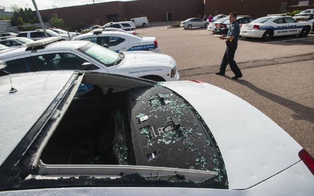 Police Sgt. Kory Dabb accesses the damage to the fleet of police cars at the Stetson Hills police station Friday morning, July 29, 2016, after a Thursday night hail storms damaged more than two dozen vehicles.