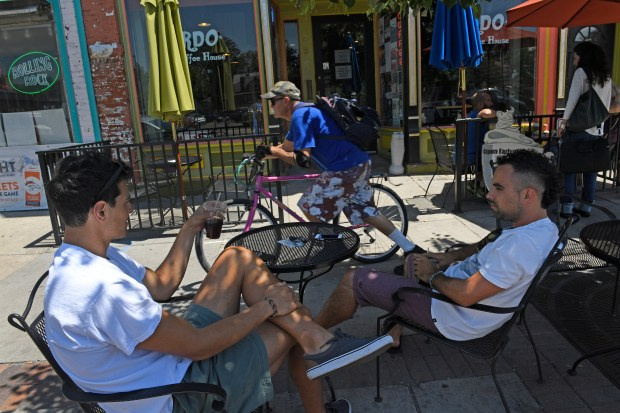 Ian Revo, left, and Luke Gottlieb, right, enjoy the shade and a cup of coffee at Bardo Coffee House as a cyclist cruises by on his bike on the sidewalk along Broadway between West Cedar and West Byers place on July 27, 2016 in Denver.