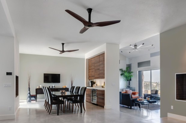 This photo provided by courtesy of Big Ass Fans shows the Haiku ceiling fan in a dining room. Energy Star recognizes it as the top-ranked fan in energy efficiency. Haiku is available with SenseME, an onboard computer that automates comfort based on temperature, humidity and user preferences. SenseME also has an occupancy sensor, turning the fan off automatically when you leave the room to save even more energy. (Jeff Kroeze/Big Ass Fans via AP)