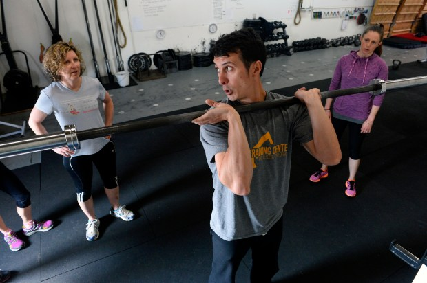 Instructor Mike Thurk shows the correct form for lifting weights to Jane Beitler, left, and Elizabeth Carey during training at the Alpine Training Center in Boulder.