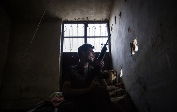 A 23-year old fighter and ex-US marine from the US, nick-named by Kurdish fighters as Hewal Agir, guards a look out point during clashes with Islamic State (IS) group fighters on April 17, 2015, in the outskirts of the north-western Syrian town of Tal Tamr, north of Hasakeh, near the border with Turkey, as he fights alongside People Protection Unit (YPG) fighters under the commanders, Sider and Gerzan. International fighters, some of whom are former members of the military and others with zero combat experience came to Syria to help Kurdish forces in their fight against Islamic State (IS) group jihadists. Since very few YPG fighters speak English, the foreign fighters are mostly assigned together in troops. AFP PHOTO / UYGAR ONDER SIMSEK (Photo credit should read UYGAR ONDER SIMSEK/AFP/Getty Images)