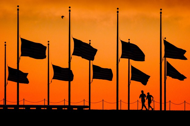 In this June 13, 2016 file photo, flags fly at half-staff around the Washington Monument at daybreak in Washington, by order of President Obama, the day after more than four dozen people were killed in the Orlando, Fla., nightclub shootings.