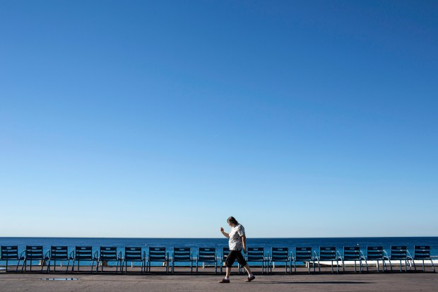 A woman walks on the Promenade des Anglais in Nice, southern France, Saturday, July 16, 2016. Nice's seaside boulevard reopens to traffic Saturday following a dramatic truck attack which killed more than 80 people and wounded more than 200 others at a fireworks display.