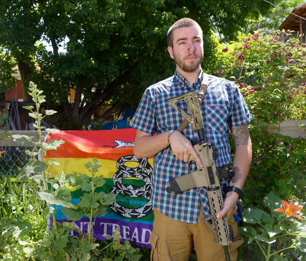 Matt Schlentz poses with his Rainbow-Gadsen Flag and AR-15 in his backyard in Salt Lake City, Wednesday, June 16, 2016. Schlentz is the Pink Pistols Utah chapter President and said Pink Pistols, a national LGBT pro-gun rights organization, membership has grown from 1,500 to 4,000 since Omar Mateen's June 12 rampage in Orlando, Fla.