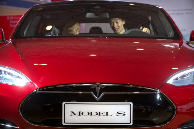 In this Monday, April 25, 2016, file photo, a man sits behind the steering wheel of a Tesla Model S electric car on display at the Beijing International Automotive Exhibition in Beijing.