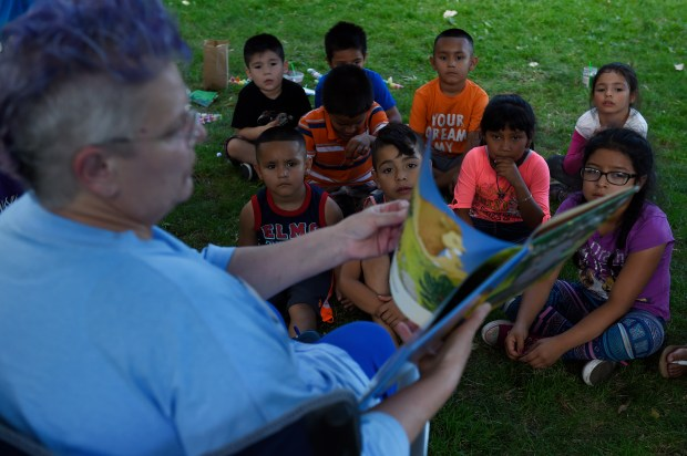 Library program associate Heidi Becker reads a book to children during the Westwood Summer Youth Camp at Westwood Park in Denver, Colorado on July 5, 2016. The Denver City Council will hear the Westwood neighborhood plan on July 18th. Photo by Seth McConnell, YourHub
