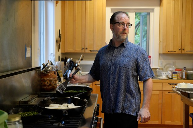 Thaddeus Cummins looks to a fellow community member while preparing dinner in the Common House at Hearthstone Co-Housing Community on July 21, 2016, in Denver, Colorado. Hearthstone Co-Housing Community incorporates 33 town home units as well as a common house and common green areas. A new co-housing community, Aria Co-Housing, will be built at the former Marycrest convent site at the intersection of Federal Boulevard and West 52nd Avenue. (Photo by Anya Semenoff/The Denver Post)