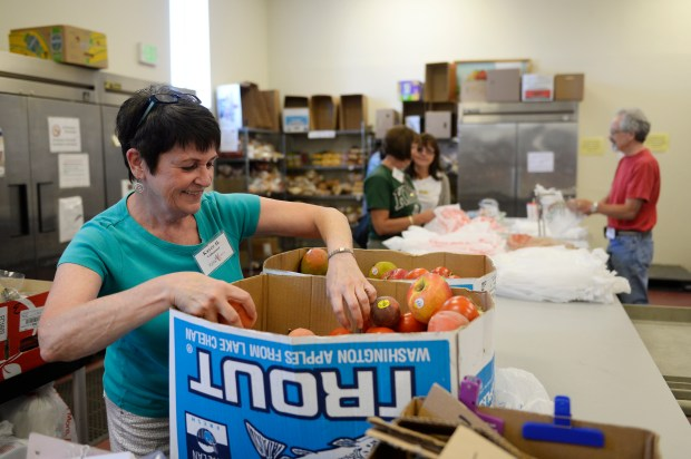 CASTLE ROCK, CO - JULY 20: Kayce Healy, a volunteer at Douglas/Elbert Task Force, sorts through donated produce in the organization's food bank on July 20, 2016, in Castle Rock, Colorado. Castle Rock Town Council and Douglas County Commissioners voted to not receive federal block grants in the coming year. Douglas/Elbert Task Force will lose grant funding due to the decision. (Photo by Anya Semenoff/The Denver Post)