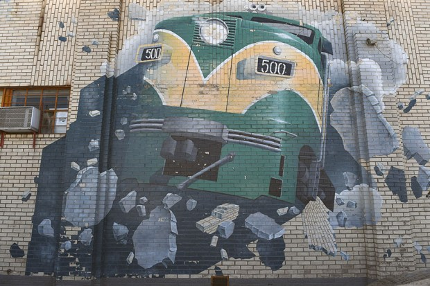 The well known painting of a train coming out of a brick wall is seen on the outside of the Caboose Hobbies store on August 14, 2016 in Denver, Colorado.