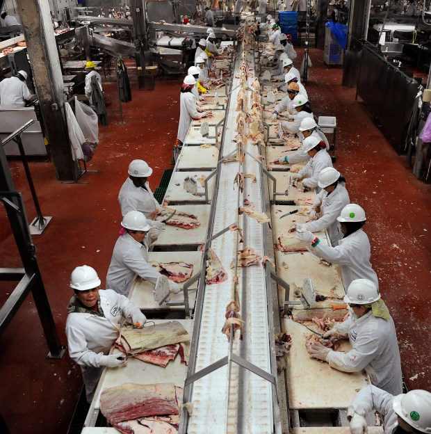 Workers trim beef at Cargill Meat Solutions in Fort Morgan. Colorado's labor department has ruled that more than 100 Muslim workers fired from the meatpacking plant are eligible for unemployment benefits because a company cannot force workers to choose between their religion and their jobs.