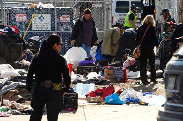 A Denver sheriff's deputy oversees the clearing of a homeless camp along Park Avenue West on March 8, 2016.