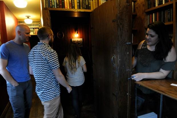 Book clerk Kristen Bair, right, admits patrons to Williams & Graham through a hidden door behind a bookcase.