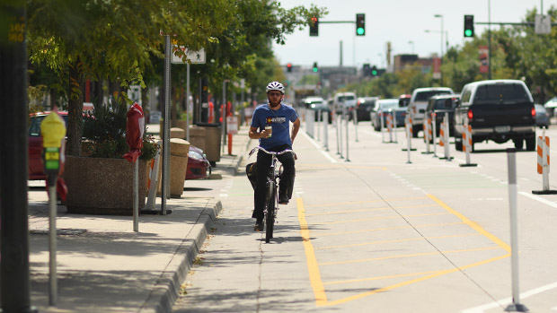 A cyclist rides along the new two-way bike lane on South Broadway in Denver earlier this year.