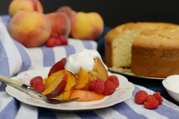 Fragrant orange and lemon cake toped with peaches, raspberries and whipped cream