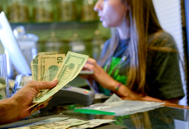 A customer counts out cash for a transaction at the Native Roots pot shop in Boulder County. Marijuana sales in Colorado are subject to the regular state sales tax of 2.9 percent. In addition, recreational sales are subject to a special 15 percent excise tax and a 10 percent sales tax.