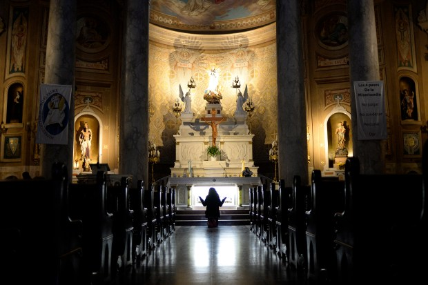 A woman prays in front of the altar after Sunday mass in Belgrano, Buenos Aires, Argentina June 26, 2016.