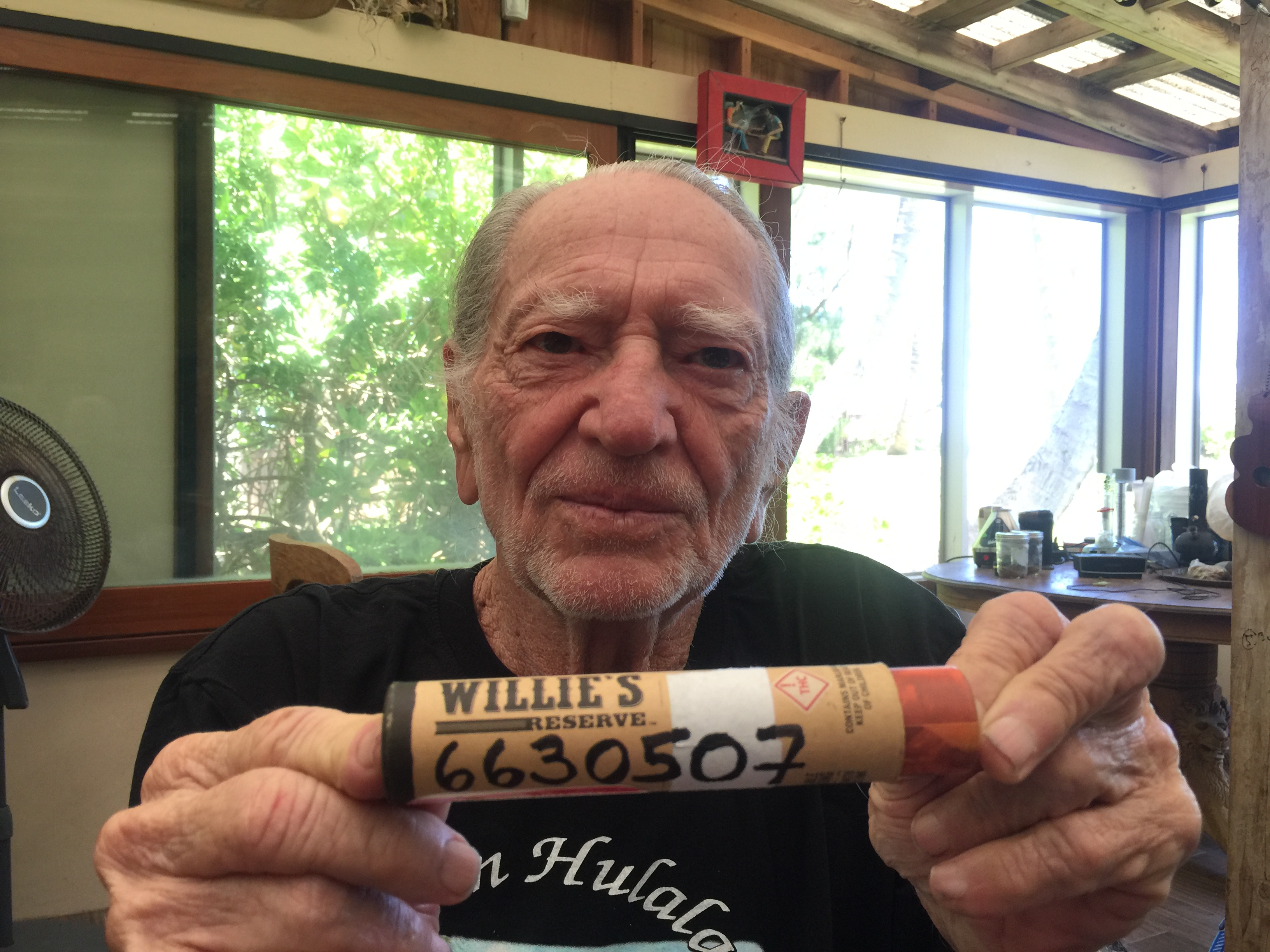 "Willie Nelson holds up a container of his branded marijuana with ""6630507"" written on it."