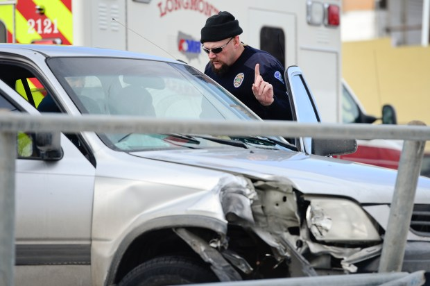 Longmont Master Police Officer Kris Ford administers a road side sobriety test to the driver of a SUV that drove into a fence, Monday, Jan. 5, 2015, on the 600 Block of Main Street in Longmont.