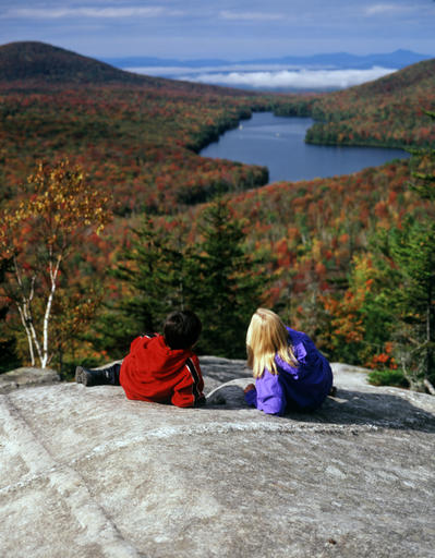 People take in the fall foliage from Owls Head Mountain in Groton State Forest in Vermont. Kettle Pond is seen in the distance.