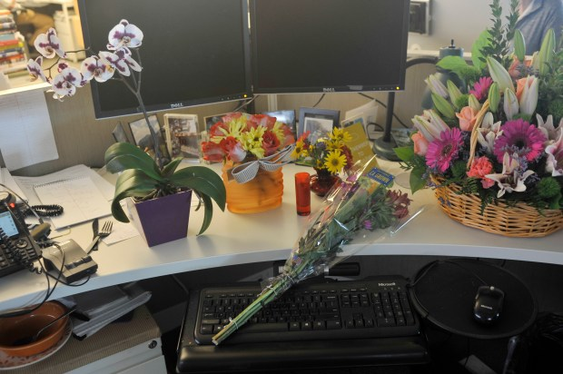 Flowers sit on the desk of Denver Post reporter Colleen O'Connor