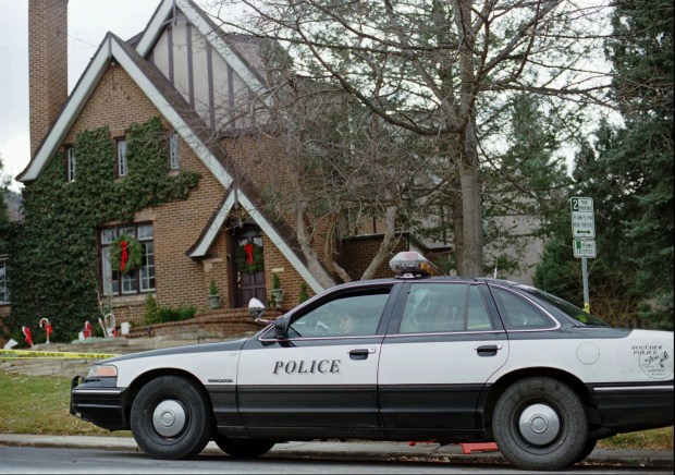 A police officer sits in her cruiser on Jan. 3, 1997, outside the home in which 6-year-old JonBenet Ramsey was found murdered in Boulder.