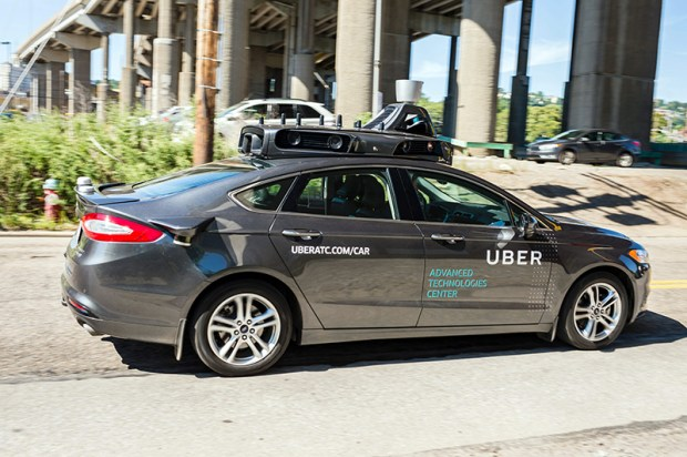 A pilot model of an Uber self-driving car drives down a street on Tuesday in Pittsburgh.
