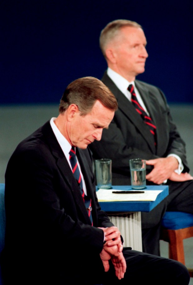 In this Oct. 15, 1992, file photo President George H.W. Bush looks at his watch during the 1992 presidential campaign debate with other candidates, Independent Ross Perot, top, and Democrat Bill Clinton, at the University of Richmond, Va.