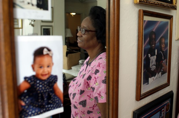 In this photo taken Oct. 18, 2016, Gwen Strowbridge, 71, poses for a photograph among photos of her grandchildren wearing her work uniform at her home in Deerfield Beach, Fla. Strowbridge works six days a week caring for a 100-year-old woman. She has worked all her life and plans to work until she can't physically work anymore. (AP Photo/Lynne Sladky)