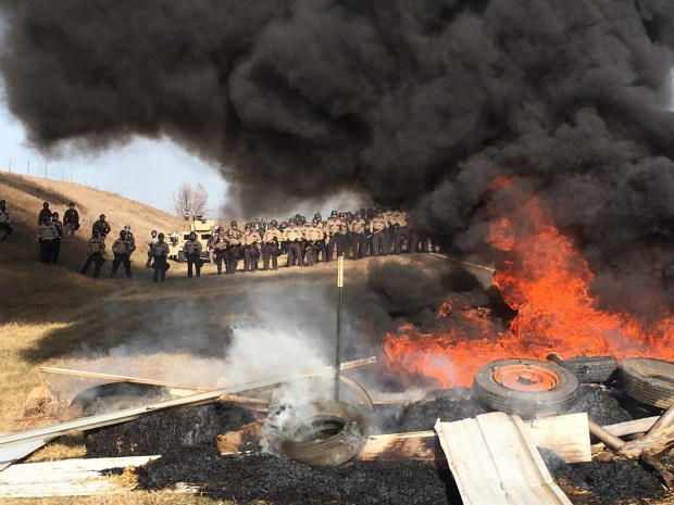 Tires burn as armed soldiers and law enforcement officers stand in formation on Oct. 27, 2016, to force Dakota Access pipeline protesters off private land where they had camped to block construction.