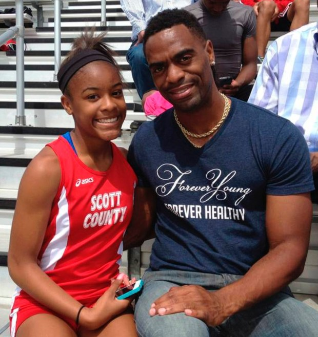In this May 3, 2014, photo, Trinity Gay, a seventh-grader racing for her Scott County High School team, poses for a photo with her father Tyson Gay, after she won the 100 meters and was part of the winning 4-by-100 and 4-by-200 relays at the meet in Georgetown, Ky. The 15-year-old daughter of Olympic sprinter Tyson Gay was fatally shot in the neck, authorities and the athlete's agent said Sunday, Oct. 16, 2016, and police have arrested a man in connection with the shooting.