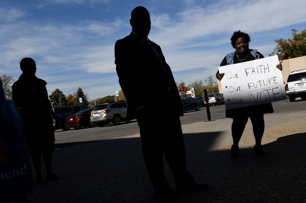 The Reverend Dr. Timothy E. Tyler, middle, and church member Ashlee Taylor, right, rally outside of the Denver Museum of Nature and Science after praying over ballots taken from their church to place into ballot boxes outside the museum on October 23, 2016 in Denver, Colorado. During their Sunday worship service the congregation prayed for the candidates and over the congregants prepared ballots. ÒIn this climate of Presidential election uncertainty and political uneasiness we believe that it is important for the African ÐAmerican Church to give leadership and to encouraged her constituents to be involved in the voting process,Ó said Dr. Timothy Tyler, Pastor of Shorter Community AME Church.