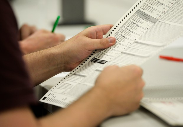 Denver Election judges survey and check voting ballots filled out by members of the Logic and Accuracy Test Board during a test of the ballot system in the counting room at the Denver Elections headquarters October 13, 2016.