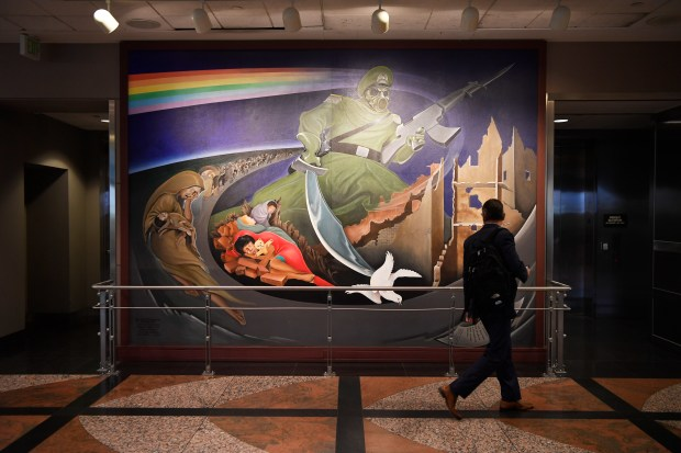 "A traveler looks over a wall mural, part of an installation at the Denver International Airport entitled, ""Children of the World Dream Peace"" October 20, 2016."