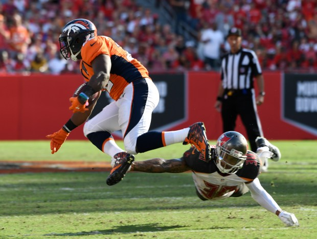 Denver Broncos running back C.J. Anderson (22) gets tripped