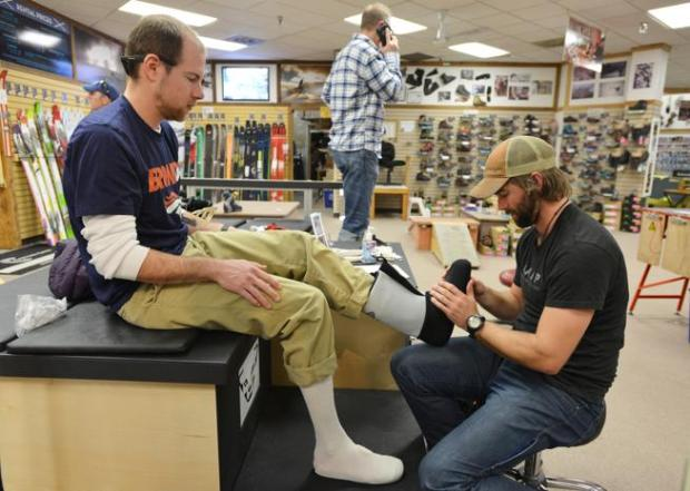 Byron Rudisill, left, begins the process of form fitting snowboard boot linings with the help of employee Eric Thomson at Neptune Mountaineering in the Table Mesa Shopping Center in this January 2016 file photo.