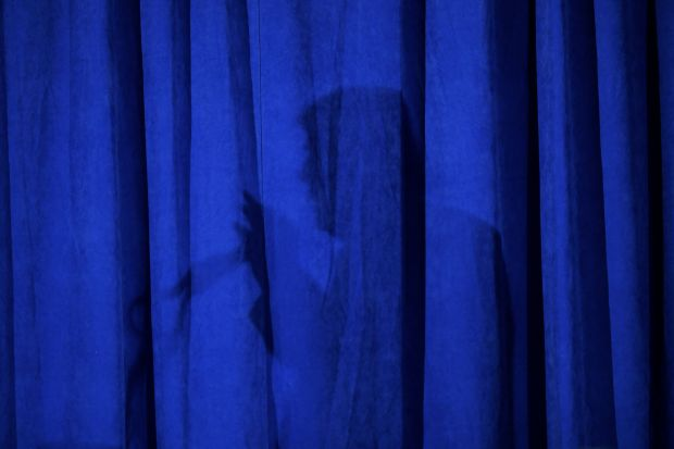 Republican presidential nominee Donald Trump casts a shadow on a curtain as he speaks on Sept. 28 in Chicago.